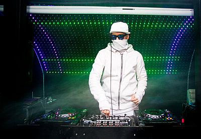 DJ playing music in nightclub - p555m1311906 by Aleksander Rubtsov