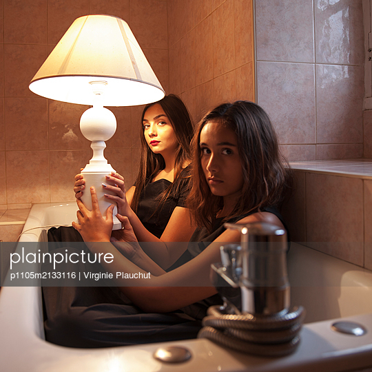 Two women with lamp in bathtub - p1105m2133116 by Virginie Plauchut
