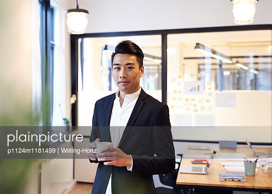 Asiatischer Mann mit Smartphone im Büro - p1124m1181499 von Willing-Holtz