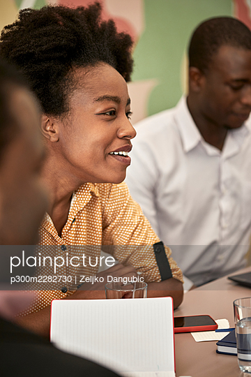 Smiling female professional looking away while sitting at desk during meeting at coworking office - p300m2282730 by Zeljko Dangubic