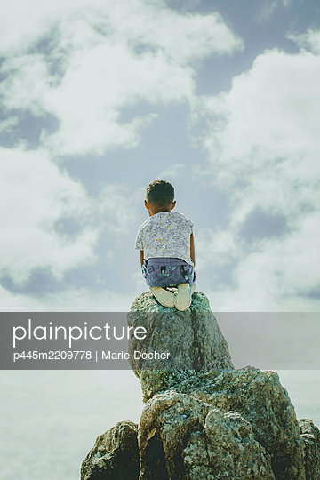 Child on a rock - p445m2209778 by Marie Docher