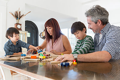 Family playing with wooden train set - p1192m1493094 by Hero Images