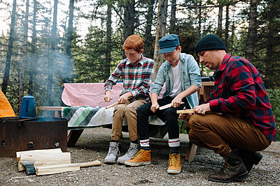Father and sons preparing firewood at campsite - p1192m2129292 by Hero Images