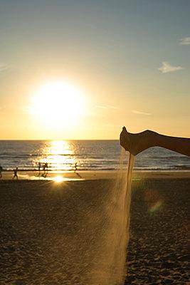 Sand rinnt duch einer Hand am Strand - p1212m1171654 von harry + lidy