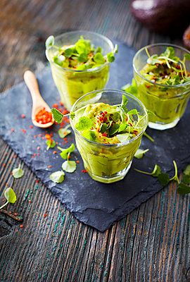 Glasses of avocado cream with chili flakes, cress and parsley - p300m1568166 von Kai Schwabe