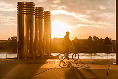 Senior woman riding city bike at the riverside at sunset - p300m2005626 by Jo Kirchherr
