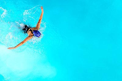 Teenage girl swimming in swimming pool - p924m807061f by Pete Saloutos