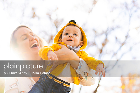 Happy mother carrying baby boy in a park - p300m2154775 by Eloisa Ramos