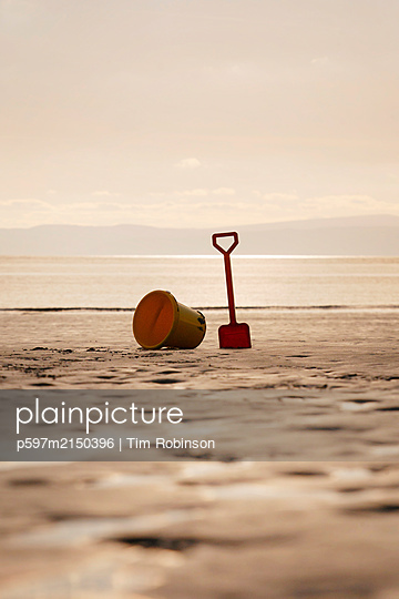 Abandoned bucket and spade on sandy beach - p597m2150396 by Tim Robinson