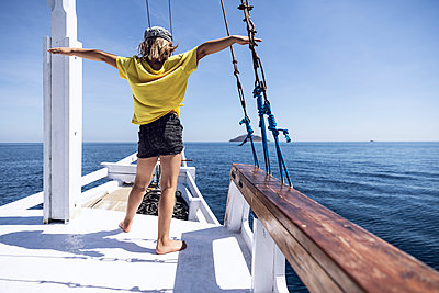 Indonesia, Komodo National Park, girl on a sailing boat - p300m2103383 von Maya Claussen