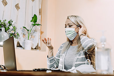 Senior woman wearing protective face mask while talking during online consultation at home - p300m2240406 by Eloisa Ramos