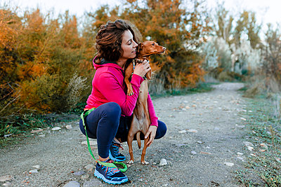 Mid adult woman looking at her dog while crouching on pathway at countryside - p300m2241495 by Manu Reyes