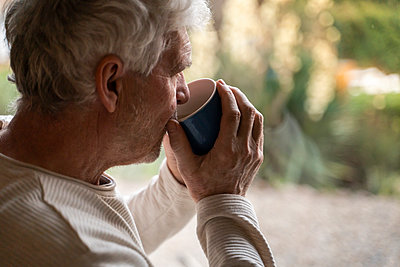 Senior man drinking coffee while standing at home - p300m2242262 by VITTA GALLERY