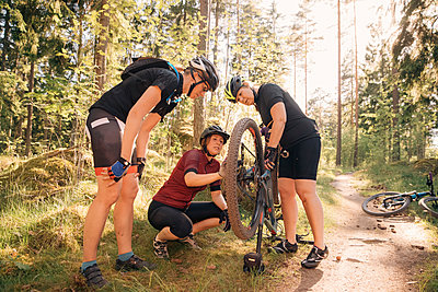 Female friends looking at woman repairing mountain bike on dirt road at forest - p426m2036736 by Katja Kircher