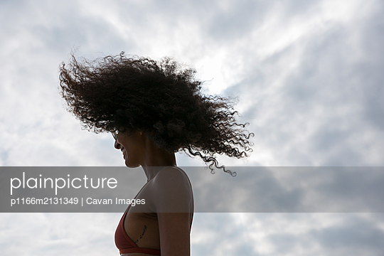 Soft silhouette of black woman flipping her big hair at the beach - p1166m2131349 by Cavan Images