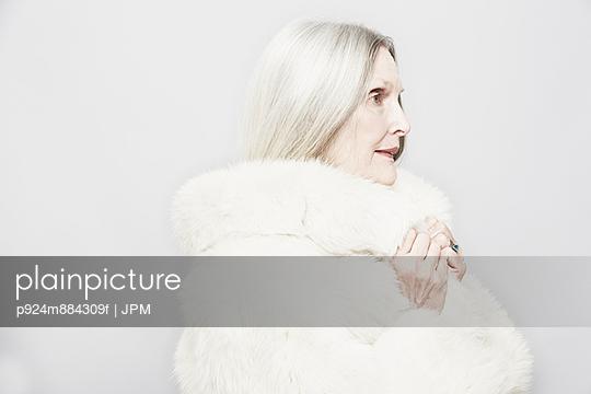 Studio portrait of senior woman in white fur coat - p924m884309f by JPM