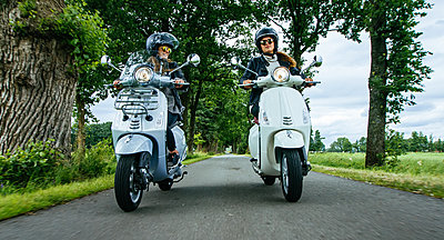 Young girls riding scooter on country road - p1053m1463164 von Joern Rynio