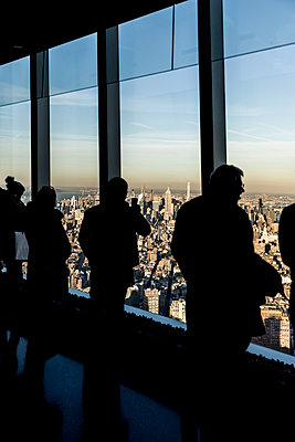 Tourists in front of a window front with view of New York - p1094m2057234 by Patrick Strattner