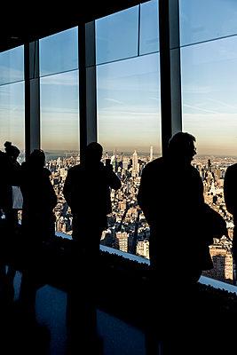 Touristen vor Fensterfront mit Blick auf New York - p1094m2057234 von Patrick Strattner