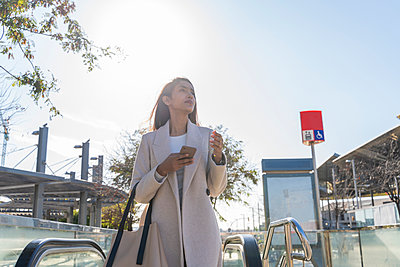 Young woman with smartphone leaving subway station - p300m2166216 by VITTA GALLERY