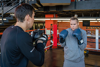Female boxer sparring with her coach in gym - p300m2171344 by Vasily Pindyurin