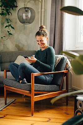 Mid adult woman smiling while using mobile phone on armchair at home - p426m2138449 by Maskot