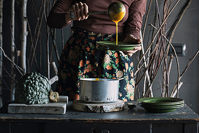 Young woman ladling fresh soup from saucepan at rustic kitchen counter, mid section - p429m2052146 by Alberto Bogo