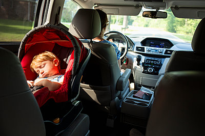Caucasian mother driving car with baby son in car seat - p555m1302059 by Roberto Westbrook