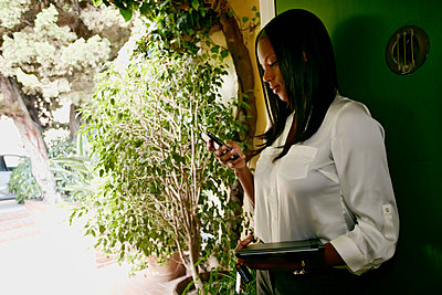 Black businesswoman using cell phone outdoors - p555m1418863 by Peathegee Inc