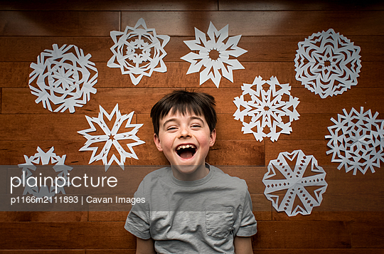High angle shot of happy boy laying on floor with paper snowflakes. - p1166m2111893 by Cavan Images