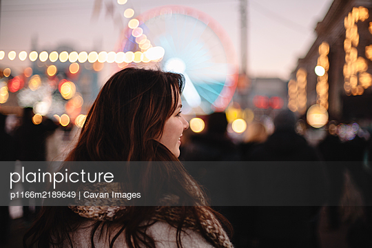 Rear view of happy teenage girl walking in Christmas market in city - p1166m2189649 by Cavan Images