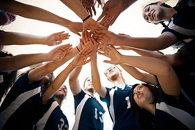 Low angle view of female sports team huddling - p1166m1087814f by Andrew Lipovsky