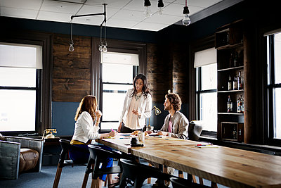 Business people discussing while sitting at desk in office - p1166m1096999f by Cavan Images