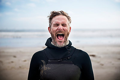 Male surfer screaming while standing at beach - p1166m1164279 by Cavan Images