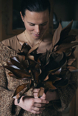 Woman with bunch of twigs with brown leaves - p300m2004091 von Alberto Bogo