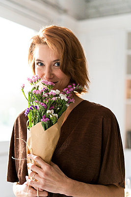 Redheaded woman smelling bunch of flowers - p300m2070122 by Eloisa Ramos