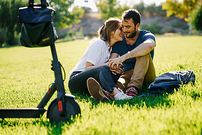 Happy couple with electric scooter relaxing on a meadow in a park - p300m2143920 by Javier Sánchez Mingorance