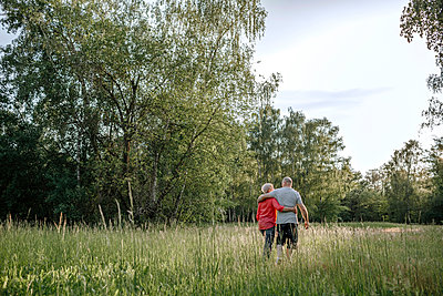 Mature couple walking along field - p300m2267845 by Oxana Guryanova