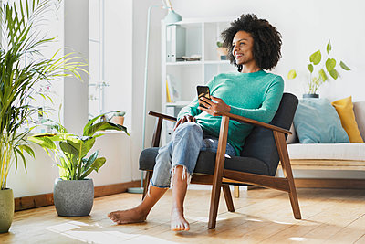 Smiling woman using mobile phone while sitting at home - p300m2276424 by Steve Brookland