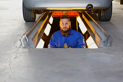 Mechanic underneath a car in Sweden - p352m2040794 by Christian Ferm