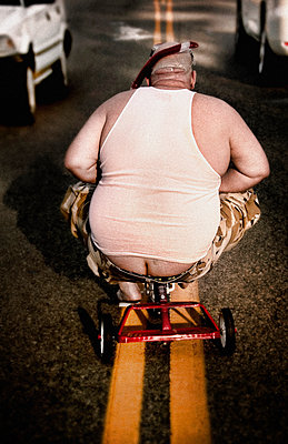 Man riding tricycle in street  - p555m1305703 by Christopher Winton-Stahle
