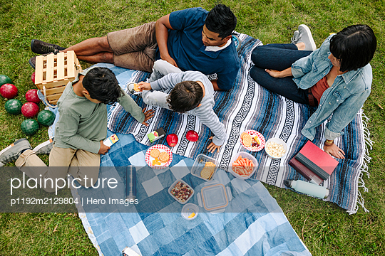 Overhead view of family having picnic in urban park - p1192m2129804 by Hero Images