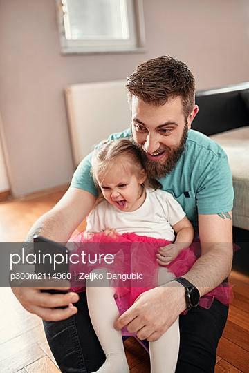 Father and daughter taking a selfie, girl wearing pink tutu - p300m2114960 von Zeljko Dangubic