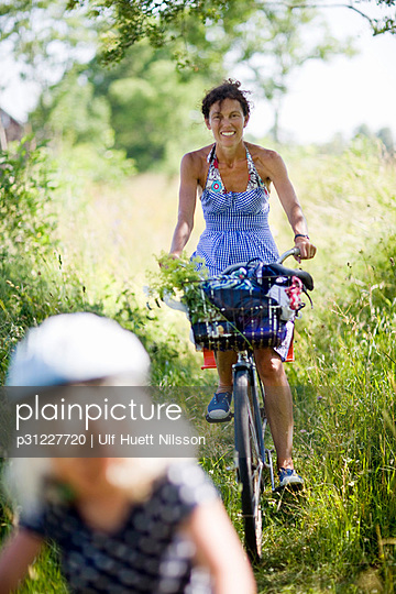 Mother and daughter riding bicycle - p31227720 by Ulf Huett Nilsson