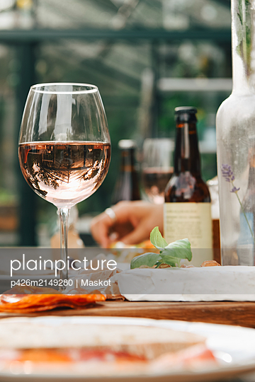 Close-up of wineglass by food on dining table at yard - p426m2149280 by Maskot
