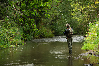 Man fly fishing at tranquil green river - p1023m2262075 by Martin Barraud