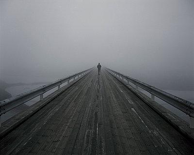 Man walking on a bridge; South Iceland - p1028m755018 by Jean Marmeisse