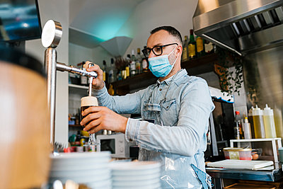 Waiter filling beer in glass in a bar during pandemic - p300m2275036 by Ezequiel Giménez