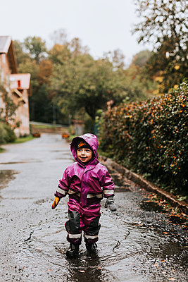 Happy toddler girl standing in puddle - p312m2239725 by Jennifer Nilsson