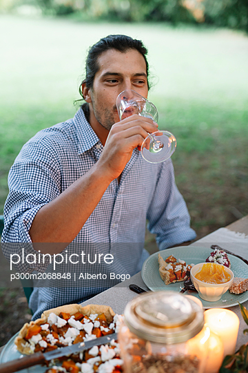 Man drinking glass of wine at garden table - p300m2068848 by Alberto Bogo